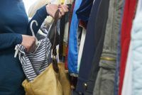 woman in store putting a striped shirt into her purse stealthily