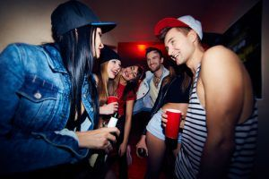 Young adults drinking at a house party